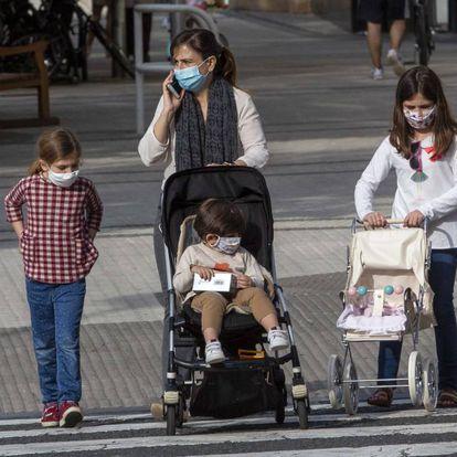 Una madre con tres niños, con mascarilla, pasea por San Sebastián.