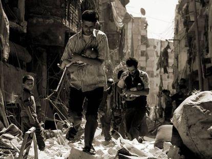 Unos alepinos llevan a unos bebés entre los escombros, a principios del pasado septiembre.