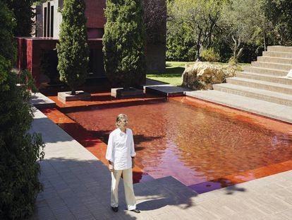 Ricardo Bofill junto a la piscina roja. Tras los cipreses la estructura cúbica acristalada, también roja, hace las veces de comedor.
