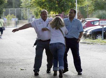 Dos vigilantes de seguridad impiden a la madre de Sandra Palo, María del Mar Bermúdez, entrar en el centro de menores.