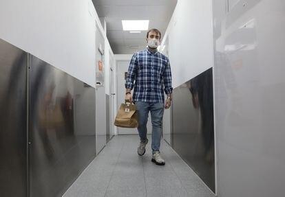 """Juan Diego Gaitán lleva un pedido desde su """"cocina fantasma"""" hasta la sala de espera del local donde lo espera un repartidor"""