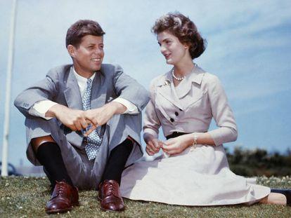 John F. Kennedy y Jacqueline Bouvier sentados en el jardín de la casa de la familia Kennedy unos meses antes de celebrar su boda.