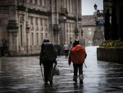 Peregrinos deambulan este domingo por Santiago tras el cierre de todos los albergues.