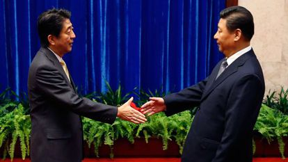 Abe (izq), primer ministro japonés, saluda a Jinping, su homólogo chino.