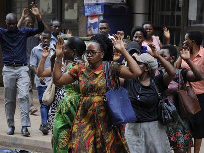 Un grupo de ugandeses levanta las manos durante la persecución policial de manifestantes pro Bobi Wine, este lunes en Kampala.