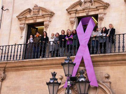 Un lazo morada en la fachada del Ayuntamiento de Palma en apoyo al Día de la Mujer.