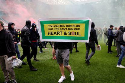 """Un aficionado del United, en Old Trafford con una cartel que dice: """"Tú puedes comprar nuestro club, pero no nuestro corazón y nuestra alma""""."""