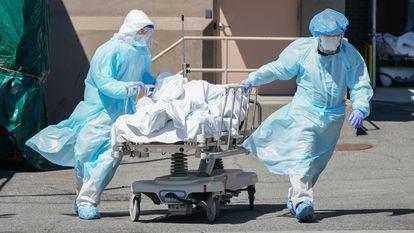 Dos sanitarios trasladan un cadáver en el hospital Wyckoff de Nueva York, en abril.