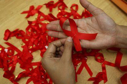 Una joven prepara lazos rojos en una campaña para la prevención del sida.