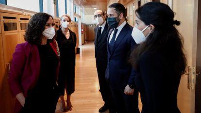 La presidenta de la Comunidad de Madrid, Isabel Díaz Ayuso conversa con la portavoz de Vox en la Asamblea, Rocío Monasterio en presencia del líder de Vox, Santiago Abascal.