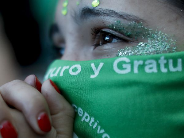 Abortion-rights activists watch a big screen showing lawmakers in session outside Congress in Buenos Aires, Argentina, Friday, Dec. 11, 2020. The Argentine lower house has approved a bill that would legalize abortion. The bill now moves to the Senate. (AP Photo/Natacha Pisarenko)