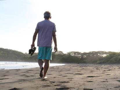 Un hombre pasea por la playa.