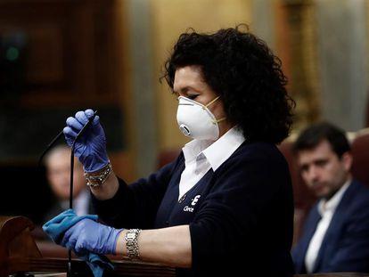 Una trabajadora desinfecta el atril del Congreso de los Diputados en el pleno de este miércoles.