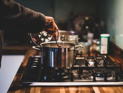 Un hombre prepara comida en una olla.