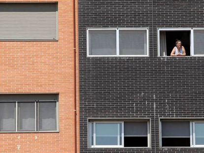 Una vecina se asoma a una ventana del edificio Memoria, de la EMVS, en la calle de Barrileros.