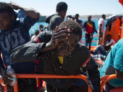 Un migrante rescatado de una patera se refresca mientras espera ser trasladado al puerto de Tarifa.