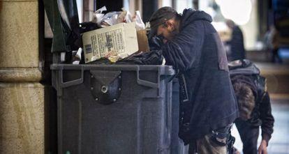 Una persona rebusca en la basura en Barcelona.