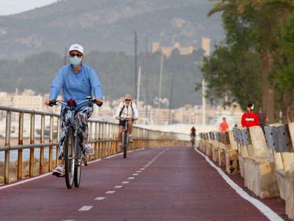 Varios ciclistas circulan por el paseo marítimo de Palma de Mallorca.