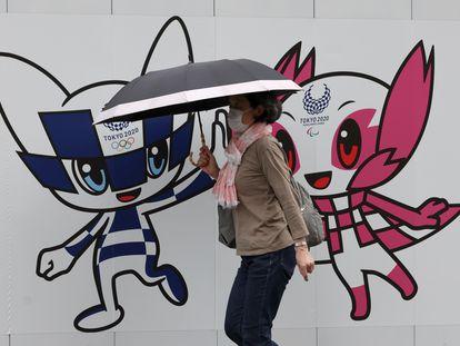 Una mujer pasea por Tokio ante una valla con las mascotas olímpicas.