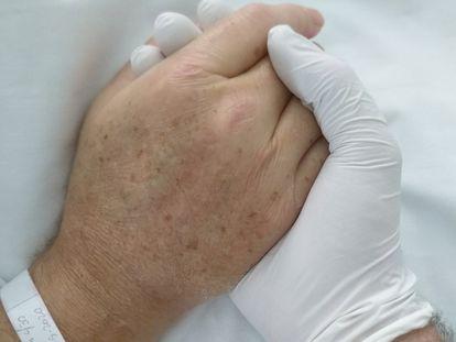 Francisco Izuzquiza coge la mano de su padre Javier en el hospital, en una imagen tomada por él mismo.