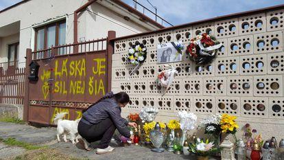 La señora Regina coloca las velas y las flores que los ciudadanos han dejado a las puertas de la casa de Kuciak y Kusnirova, en Velka Maca, el jueves.