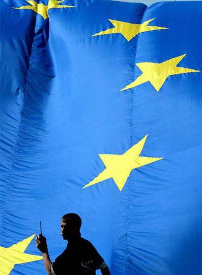 Un empleado, frente a una bandera de la UE en Bruselas.