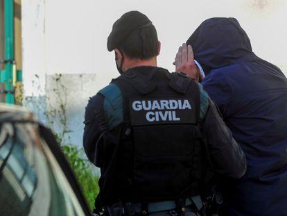 Uno de los detenidos en la operación es custodiado por un agente de la Guardia Civil.