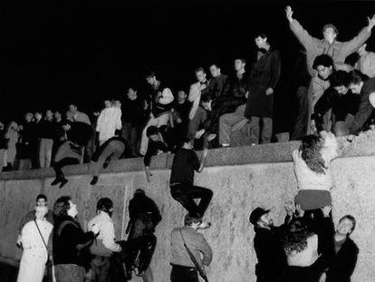 El 10 de noviembre de 1989, un grupo de jóvenes ayudan a otros a escalar el muro de Berlín.
