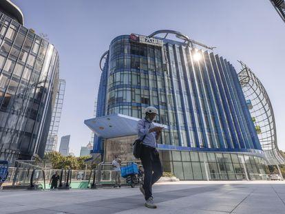 Un hombre camina junto a la sede de Evergrande en Shanghai, este jueves.