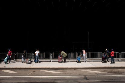 Habitantes del barrio de Brooklyn, en Nueva York ( EE UU), hacen cola para recibir paquetes de alimentos del Banco de Alimentos de la ciudad.