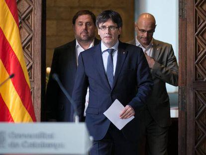 Declaración institucional del presidente catalán, Carles Puigdemont, acompañado de los consejeros Oriol Junqueras (I) y Raul Romeva (D).
