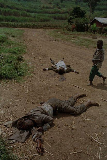 Un niño pasa junto a los cuerpos de dos hutus congoleses.