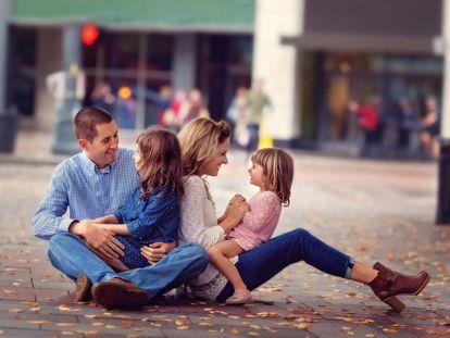 Una familia disfruta en el suelo de una vía pública.