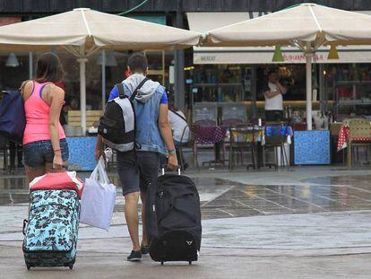 Unos turistas caminan con sus maletas por el barrio de La Barceloneta.