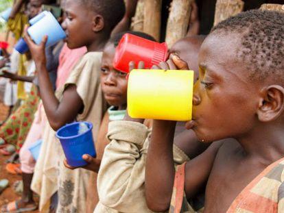Los niños toman la papilla que les sirve como complemento alimentario.
