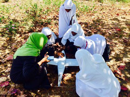 Un grupo de jóvenes recibe instrucciones de cómo usar un dron.