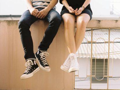 Dos adolescentes se sientan en una cornisa.