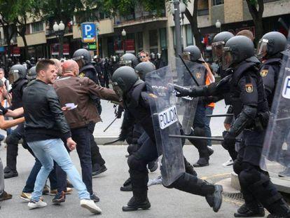 Agentes de la policía nacional intentan retirar a los concentrados en el instituto IES Tarragona.