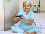 Una niña con cáncer juega a un videojuego en su habitación del hospital.