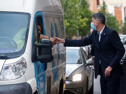 Albiol saluda a un vecino tras la visita a la sed de Cáritas en el barrio de Bufalà de Badalona.