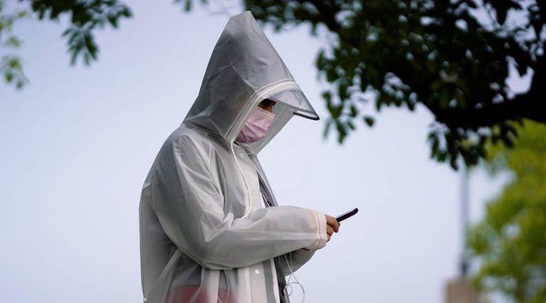 Un hombre con un equipo de protección contra la Covid-19 usa un teléfono móvil.