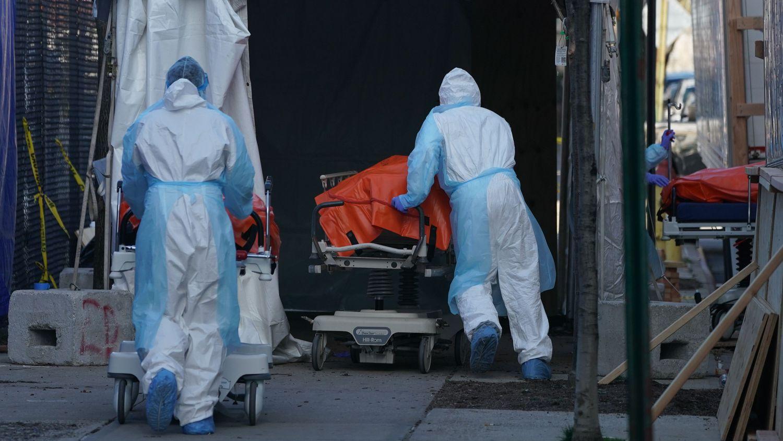 Unos trabajadores de un hospital de Brooklyn (Nueva York, EEUU) trasladan cadáveres a un camión frigorífico.