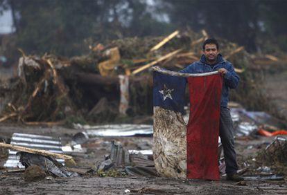 Un habitante de  Pelluhue, a unos 322 kilómetros al sureste de Santiago, muestra una enseña nacional chilena rescatada de los escombros.