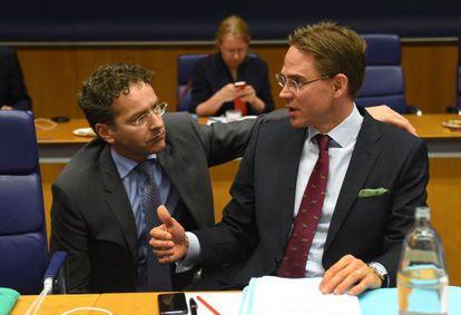 El presidente del Eurogrupo, Jeroen Dijsselbloem, agachado, habla con el finlandés Jyrki Katainen