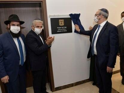 El ministro israelí de Exteriores, Yair Lapid, aplaude ante la placa que marca la inauguración de la Embajada de su país en Emiratos Árabes.