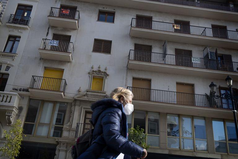 Una mujer pasa por delante de un edificio con varios pisos en venta y alquiler en Sevilla, este lunes.