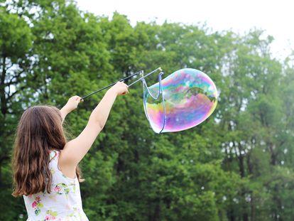 Una niña hace una pompa gigante de jabón.