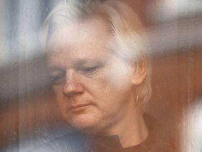Jullian Assange mira a través de la ventana de la embajada de Ecuador en una imagen tomada el 19 de mayo de 2017.