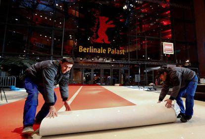 Dos trabajadores desenrollan la alfombra roja a la puerta del Palacio de la Berlinale.