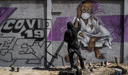 Un miembro del colectivo de graffiti senegalés RBS CREW pinta murales informativos para que los ciudadanos que no saben leer sepan cómo detener la propagación del coronavirus.